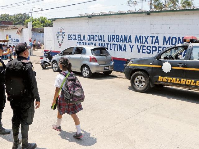 Agentes de la PNC brindan seguridad en los alrededores de la Escuela Oficial Urbana Mixta Monterrey, zona 4 de Retalhuleu, en donde se atienden dos jornadas. (Foto Prensa Libre: Rolando Miranda)