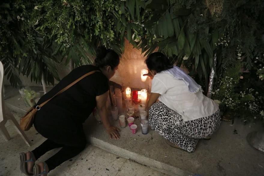 Fieles de la Iglesia de Poza Rica, Veracruz,  colocan velas en memoria de los sacerdotes asesinados. (Foto Prensa Libre: AP).