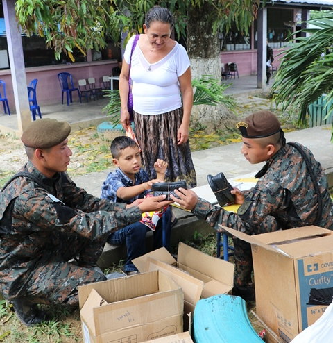 Soldados entregan zapatos, tipo crocs, a niños de escasos recursos, durante jornada médica en Melchor de Mencos, Petén. (Foto Prensa Libre: Rigoberto Escobar).