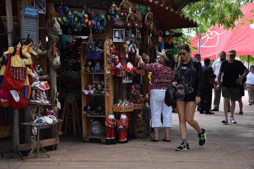 Los cruceristas que no toman una excursión, están dispuestos a comprar alguna artesanía. (Foto Prensa Libre: Enrique Paredes)