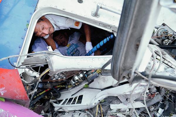 Un socorrista rescata al piloto del tráiler que se accidentó, en el km 197 de El Asintal, Retalhuleu. (Foto Prensa Libre: Jorge Tizol)