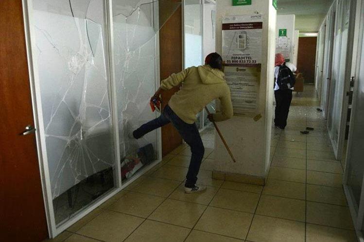 Un estudiante con el rostro cubierto causa destrozos este lunes en el interior de la Fiscalía. (Foto Prensa Libre: EFE).