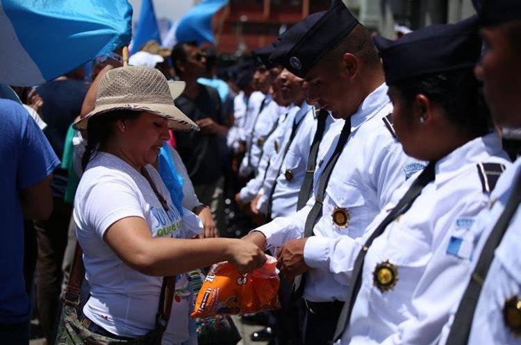 Una persona regala dulces a los agentes durante la manifestación pacífica frente al Palacio Nacional de la Cultura.