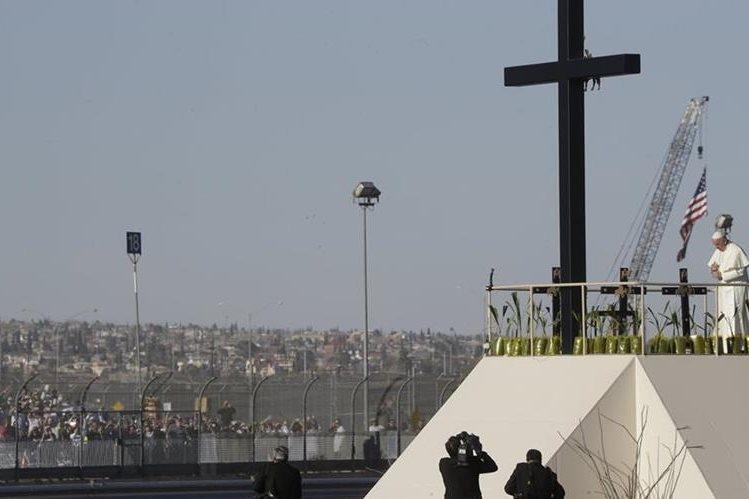 El papa Francisco, frente a una cruz eregida en homenaje a los migrantes muertos. (Foto Prensa Libre: AP).