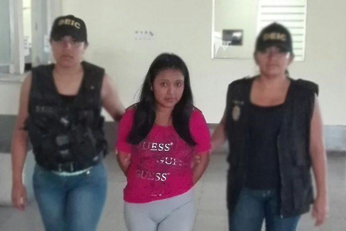 Adriana Pérez Gómez es conducida por agentes de la DEIC por parricidio en grado de tentativa y maltrato a menores. (Foto Prensa Libre: PNC)