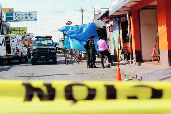 Agentes de la PNC acordonan área donde fue muerto a balazos un hombre, en una cevichería de Chimaltenango. (Foto Prensa Libre: José Rosales)