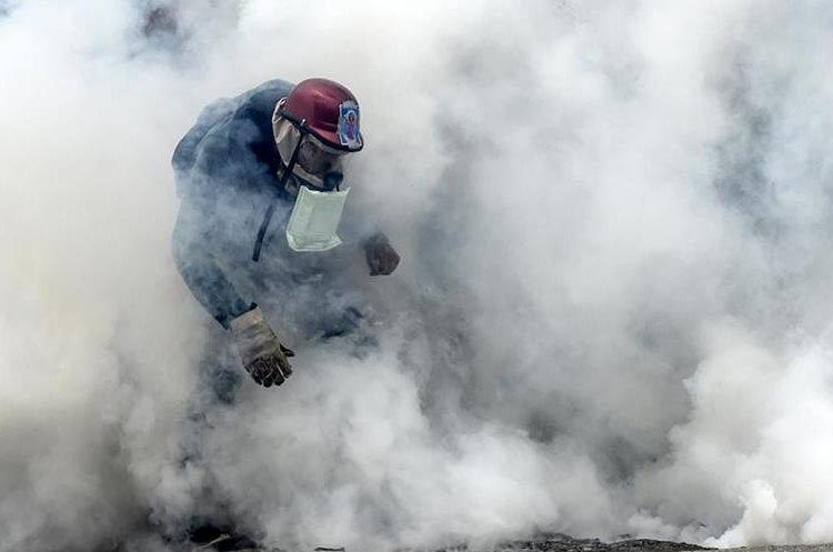 Un manifestante se protege del gas lacrimógeno lanzado por la Policía.