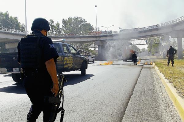 Los delincuentes quemaron simultáneamente varios vehículos robados para bloquear accesos a Guadalajara. (Foto Prensa Libre:AFP)AFP