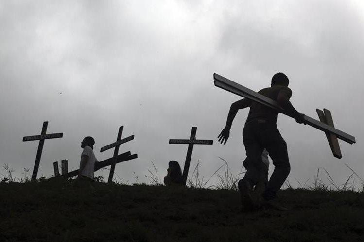 Manifestantes colocan cruces con los nombres de las personas que han muerto en protestas en Venezuela. (Foto Prensa Libre: AP)