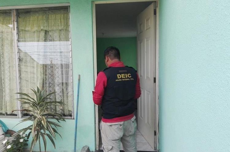 Agente de la DEIC notifica del allanamiento en una de las viviendas de los presuntos pandilleros. (Foto Prensa Libre: PNC)