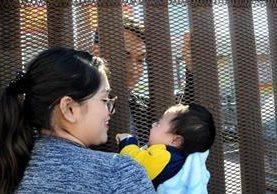 Samanta, en EE. UU. y Marco (atrás) en México, con un muro de por medio, se saluda en la frontera de Calexico. (Foto Prensa Libre: EFE).