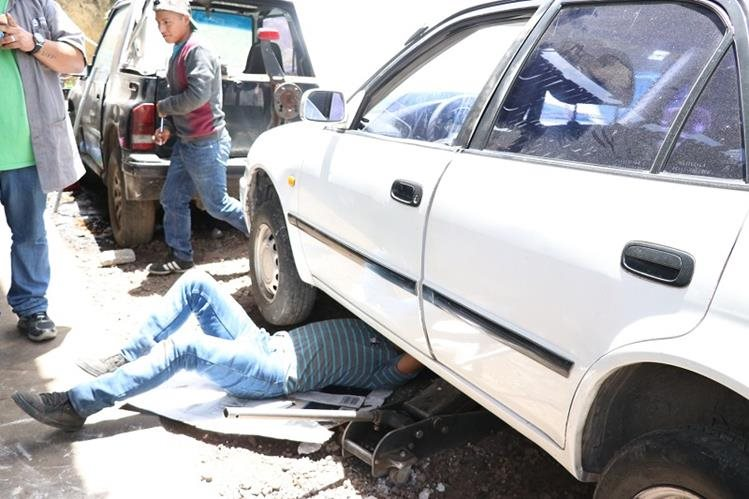 Mecánico revisa el tren delantero de un vehículo dañado por baches, en un taller de Xelajú. (Foto Prensa Libre: María José Longo)