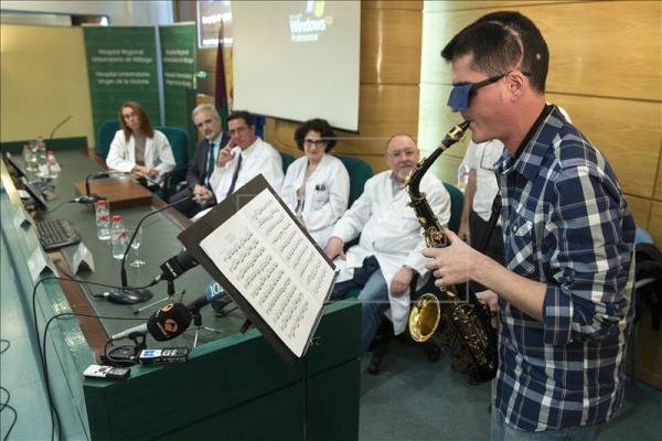 El músico, Carlos Aguilera, toca el saxo frente a los médicos que lo operaron. (Foto: www.efe.com).