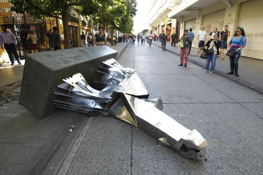 La escultura El grito de Pepo Toledo en el Paseo de la Sexta quedó en el suelo.  (Foto Prensa Libre:Paulo Raquec)