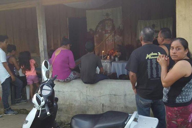 Vecinos de Poptún se reúnen en una vivienda donde una mujer asegura que en una pared de madera apareció una imagen religiosa. (Foto Prensa Libre: Walfredo Obando)