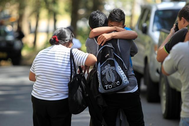 Niños se abrazan al salir del Hogar Seguro luego de incendió que mató a 19 niñas. (Foto Prensa Libre: Hemeroteca PL)