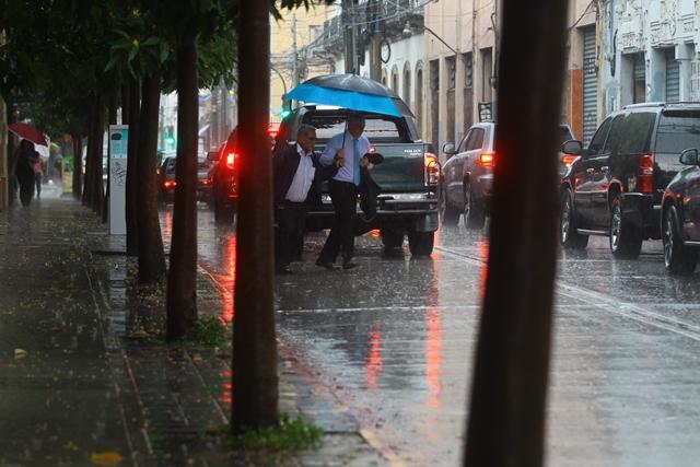Los peatones se protegen de la lluvia en las calles de la zona 1 de la ciudad de Guatemala. (Foto Prensa Libre: Hemeroteca PL)