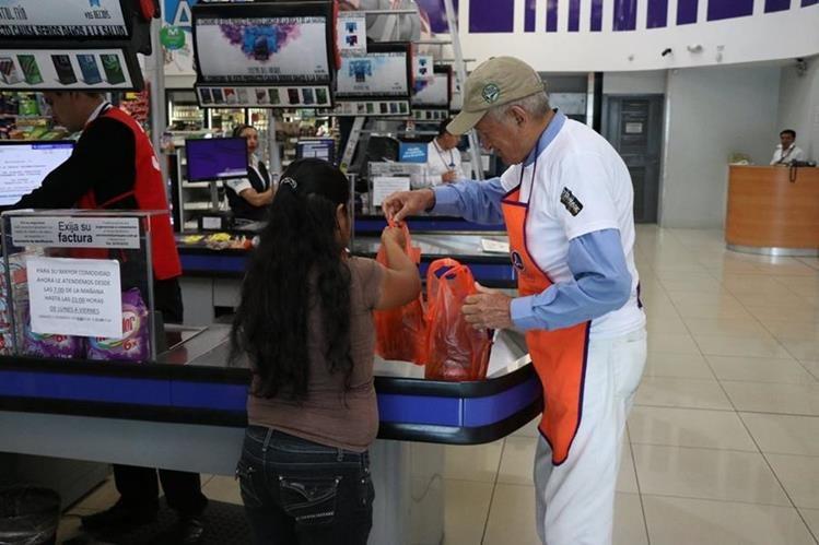 Jacobo Flores Cifuentes, de 80 años, ayuda a los clientes de La Torre, en Xela, a empacar los productos que compraron. (Foto Prensa Libre: María José Longo)