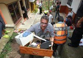 Vecinos de Tierra Nueva 1 evacuan el área por el riesgo de más derrumbes. (Foto Prensa Libre: Estuardo Paredes)