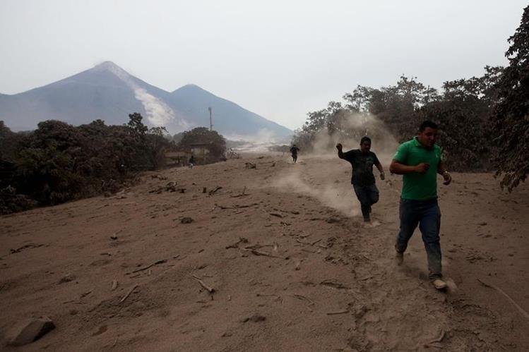 Socorristas y voluntarios corren por un deslizamiento de fluido del volcán de Fuego este lunes. (Foto Prensa Libre: EFE)