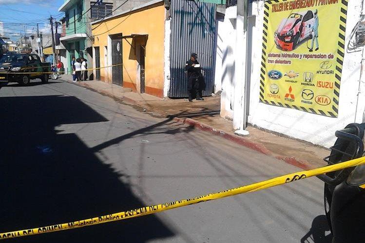 Agentes de la Policía Nacional Civil resguardan taller donde murió a balazos un trabajador, en la zona 1 de la cabecera de Chimaltenango. (Foto Prensa Libre: José Rosales)